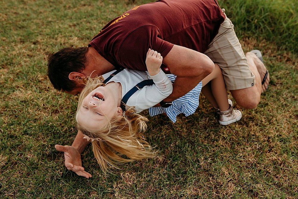 Dad tackling little girls to ground while she is laughing