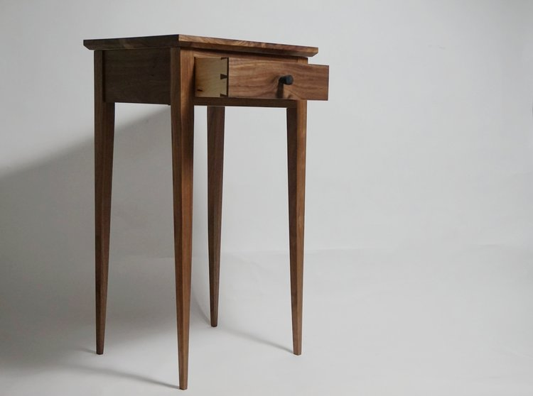 Handmade Shaker style side table with drawer.  Inspired by the simplicity of Shaker furniture, this side table mixes classic design with traditional joinery.  Materials: Walnut, beech and Ebony