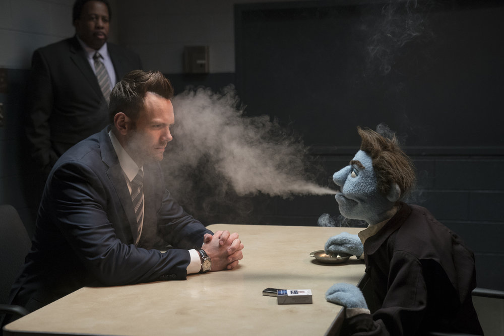 Hey, it's a living. Joel McHale gets a fateful of puppet smoke in The Happytime Murders