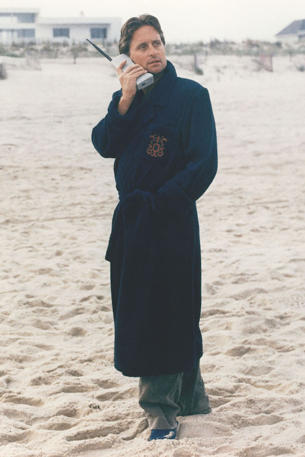 Gekko takes a business call wearing his crest-engraved dressing gown over a grey suit outside his beach house. Photograph by 20th Century Fox/Kobal/REX/Shutterstock.