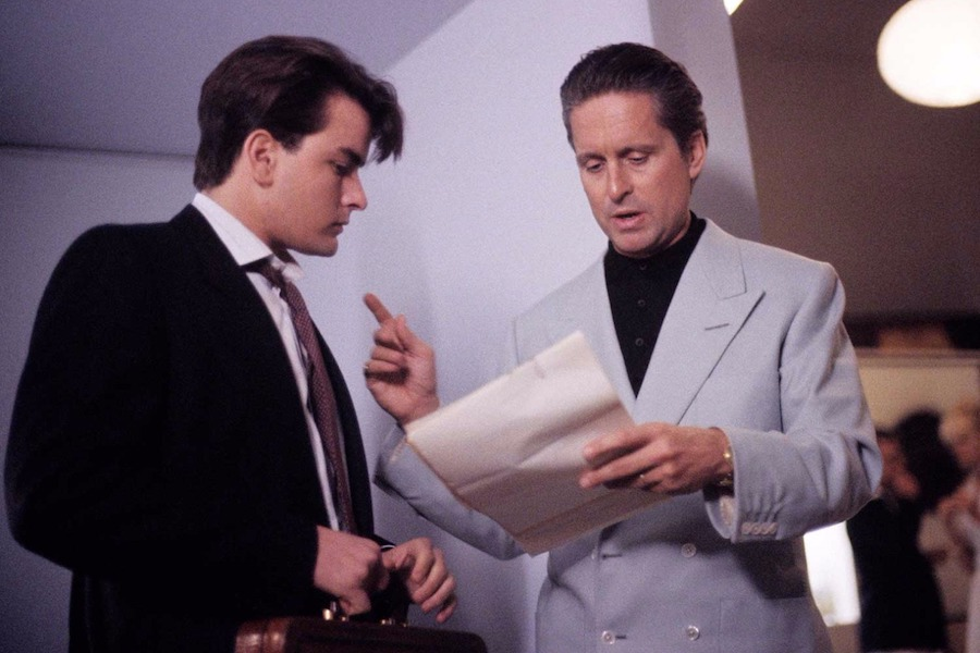 When opting for a more casual look, Gekko wears a light blue 4x2 double-breasted linen jacket [actually woolen cashmere -AF] with clear buttons over a black polo shirt. Pictured here with Bud Fox played by Charlie Sheen, 1987.