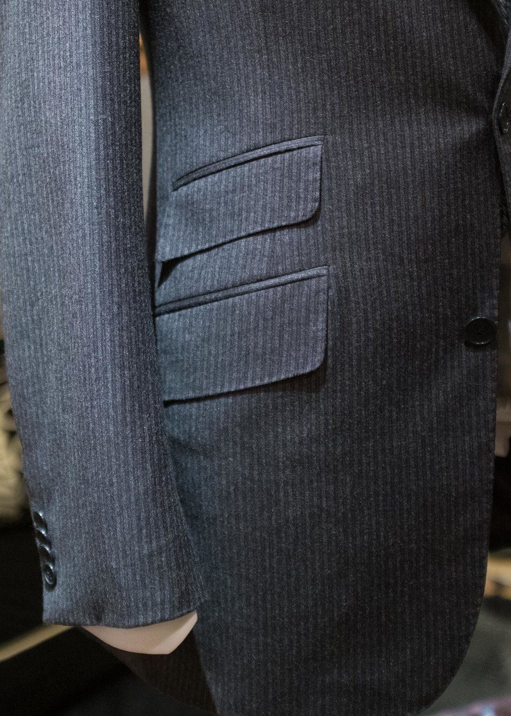 The curved front edge of this single-breasted suit jacket is reflected in the rounded front corner of the pocket flaps.