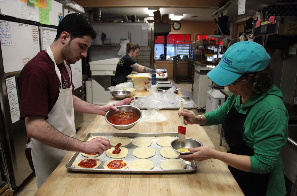 Tayara, left, spreads tomato sauce over pizza dough while Carol Yager, right, brushes the dough with egg wash.