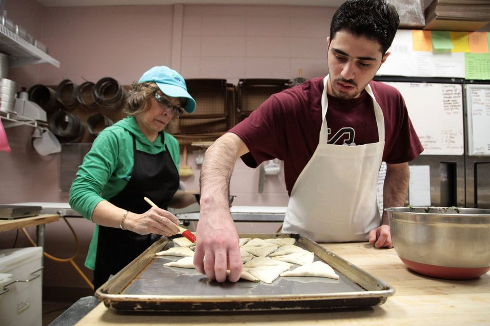 Molhem Tayara lays Spinack Fatayer, a Syrian baked good, on a baking sheet while Carol Yager, left, brushes the pastries with butter.