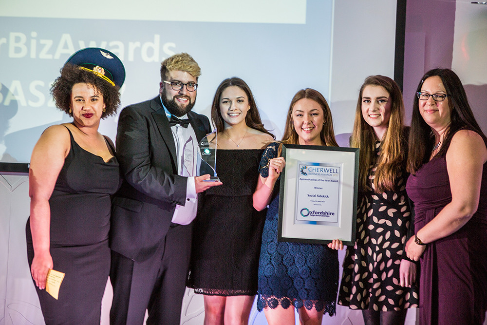 Image credit:  Pictured from left to right: Emily Bampton (Oxfordshire Apprenticeships Ambassador), Richard Hunter (Social Sidekick Digital Director), Chloe Welch, Rosie England, Nicole Faulkner (Social Sidekick apprentices) and Rachel Laycock (Social Media Team Leader). Photo credit: Vine House Studios