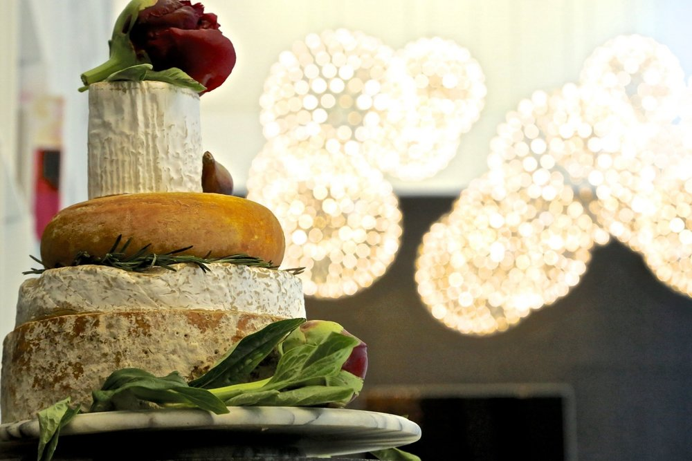 "weddinG cheese                     ""cakes""   Looking for a twist on the traditional layer cake? Our wedding cheese ""cake"" towers are made with custom selections of your favorite cheeses."