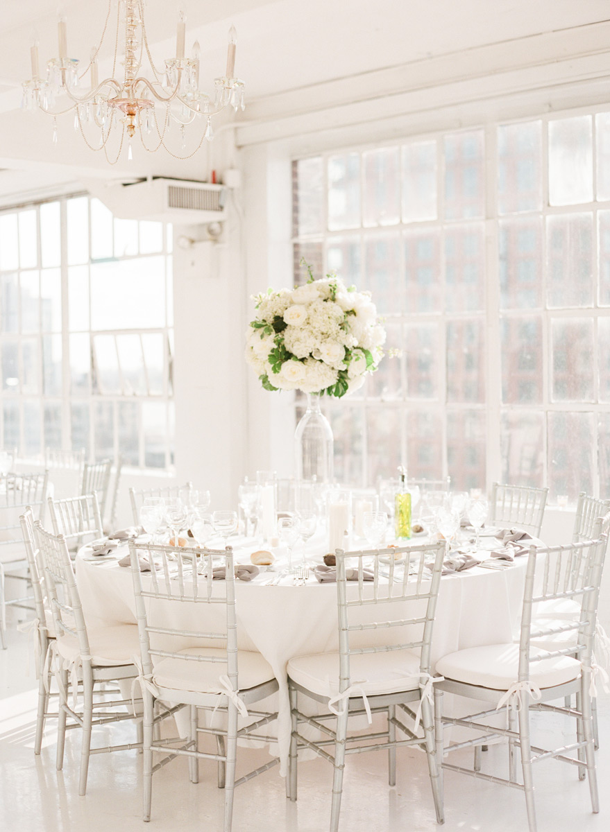 Tall white centerpiece with white roses and hydrangea