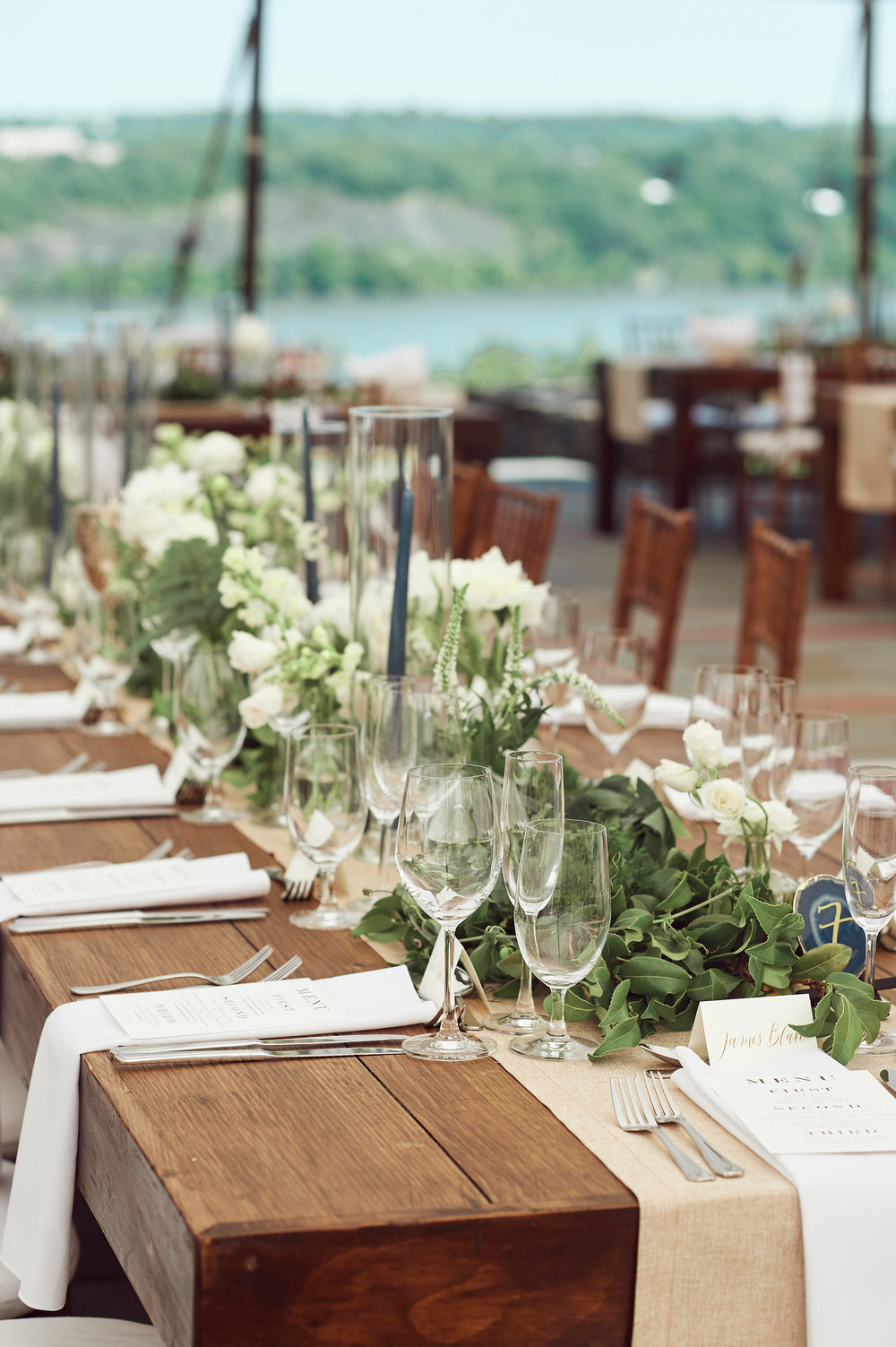 farm tables with white flowers and green garlands