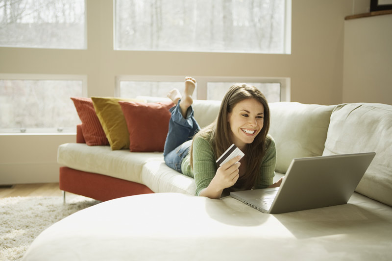Smiling woman holding her credit card while checking her online bank balance.