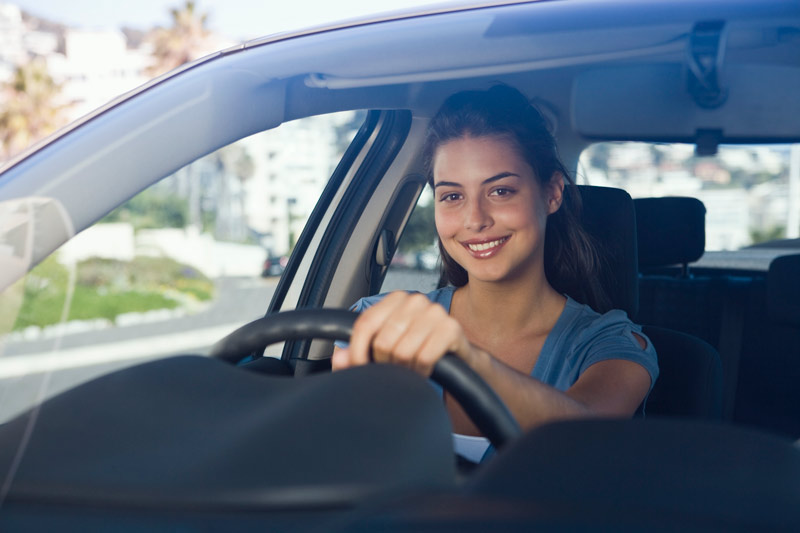 Young woman, sitting in the driver seat of a car, smiling at the camera.