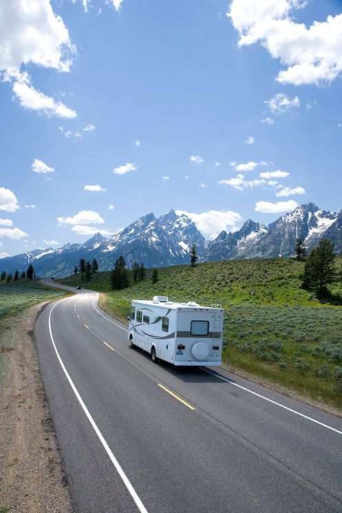 Recreational Vehicle driving into the distance, with mountains and forest in the background.