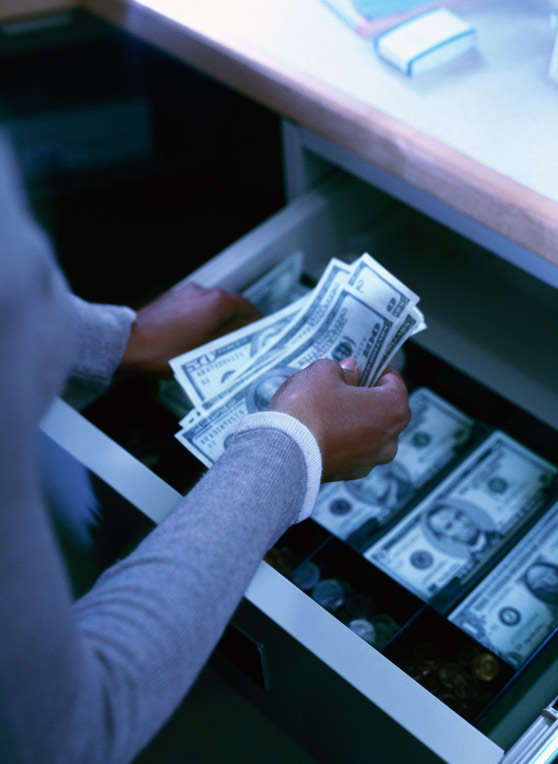 Closeup of a woman handling cash in a register.