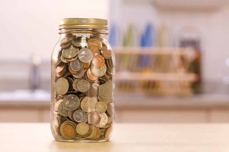 A jar of coins sitting on a desk.