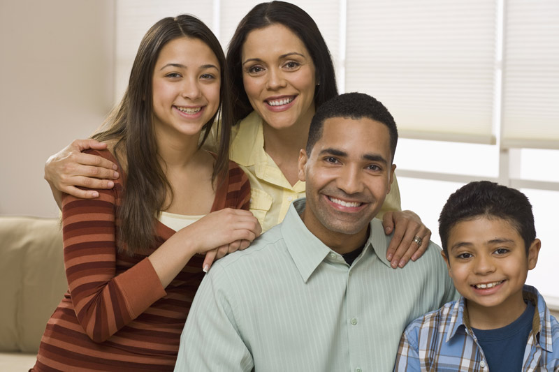 A happy family of a wife, husband, teenage daughter, and younger son.