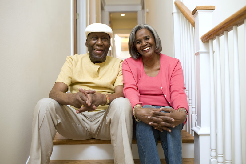 A smiling elderly couple sitting at the top of the stairs.