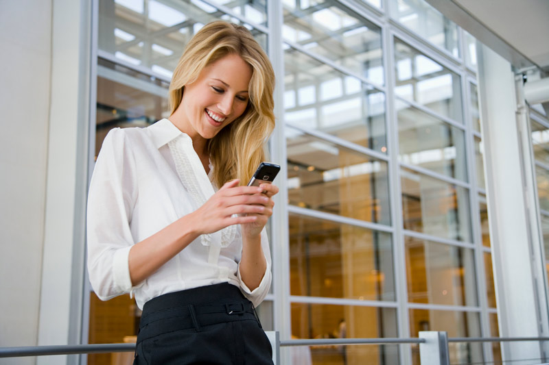 A smiling young business woman looking at her phone.