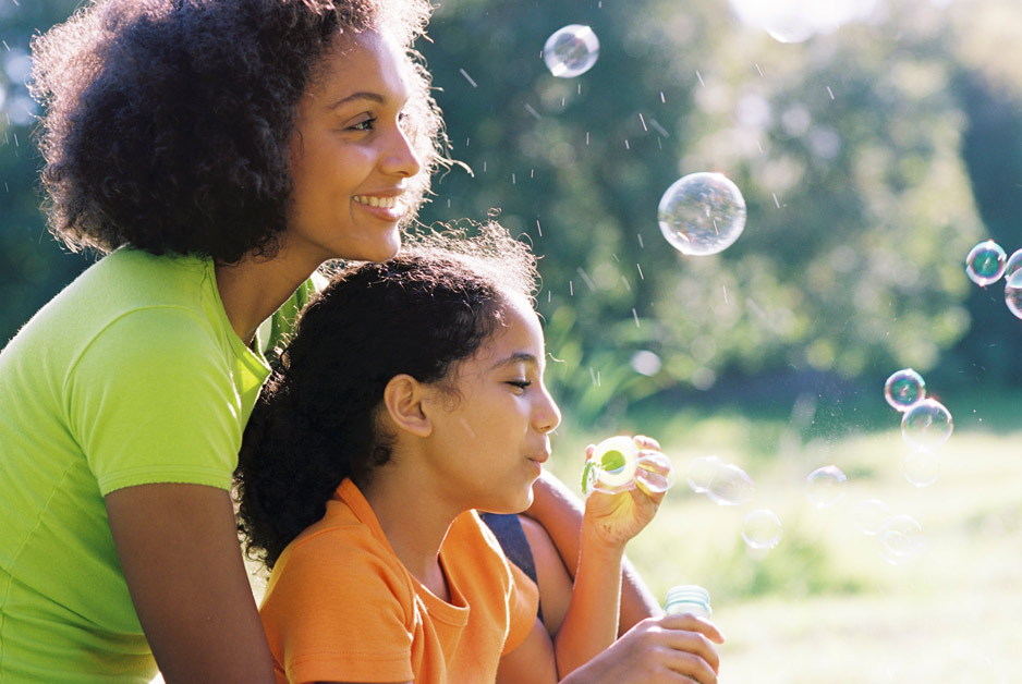 A smiling mother and daughter blowing bubbles on a summer day.