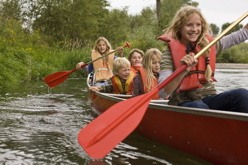 A group of happy children paddling on a canoe