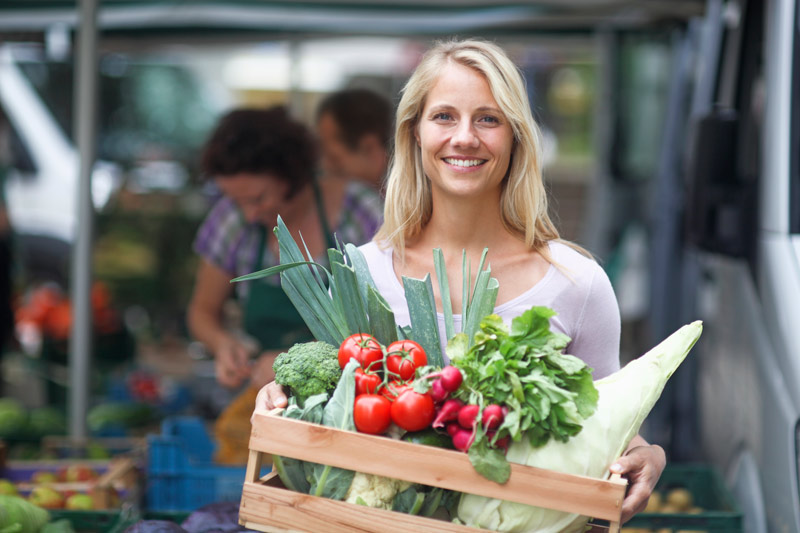 Woman shopping and carrying produce in a crate.