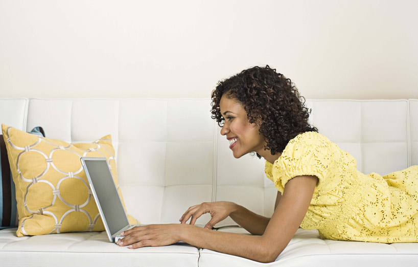 Happy woman reading her online bank statement while lying on the couch.