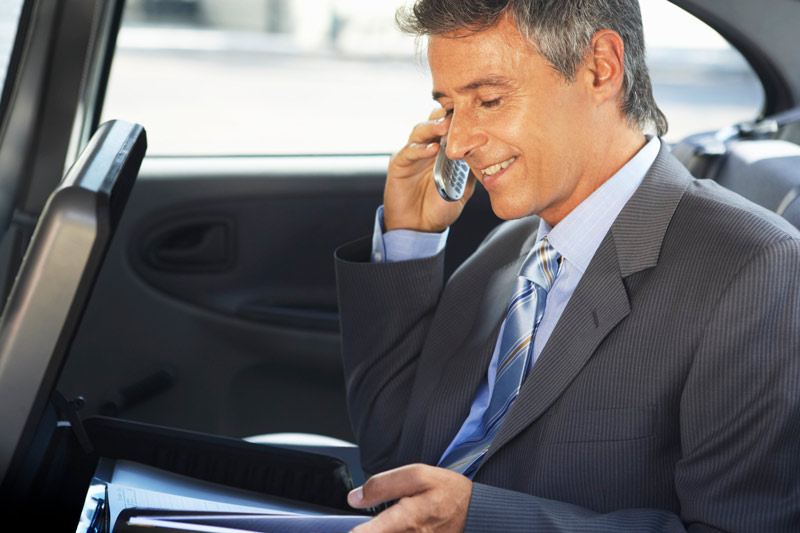 Business man talking on his cell phone, in the back seat of a car.