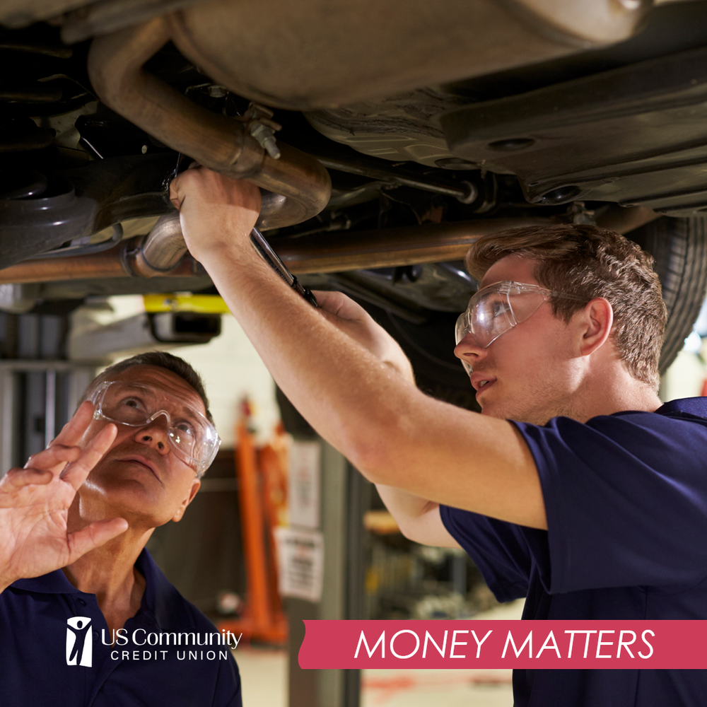 Two mechanics working on the underside of a car