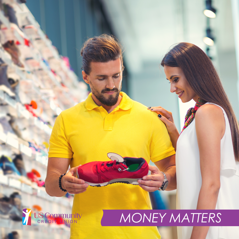 A husband and wife shopping for new shoes, with the husband holding a running shoe.