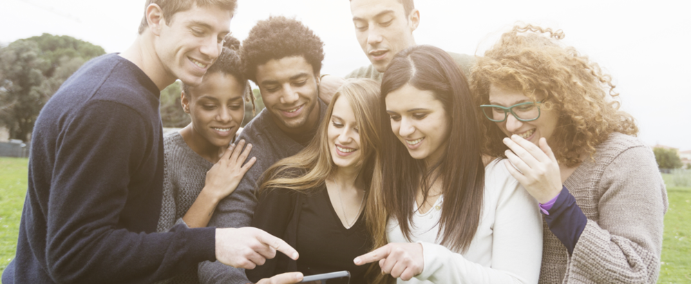 a group of millennials crowded around a smartphone