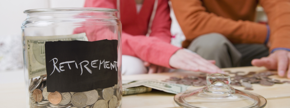 """A jar labeled """"retirement"""" with dollars and coins in it, with two people counting money in the background"""