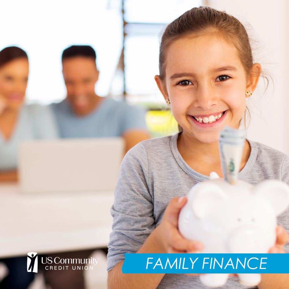 Girl holding piggy bank with money sticking out with parents looking at a laptop in the background.