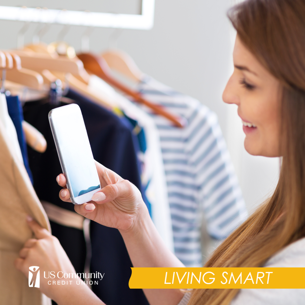 A woman looking at her smartphone while shopping for clothing