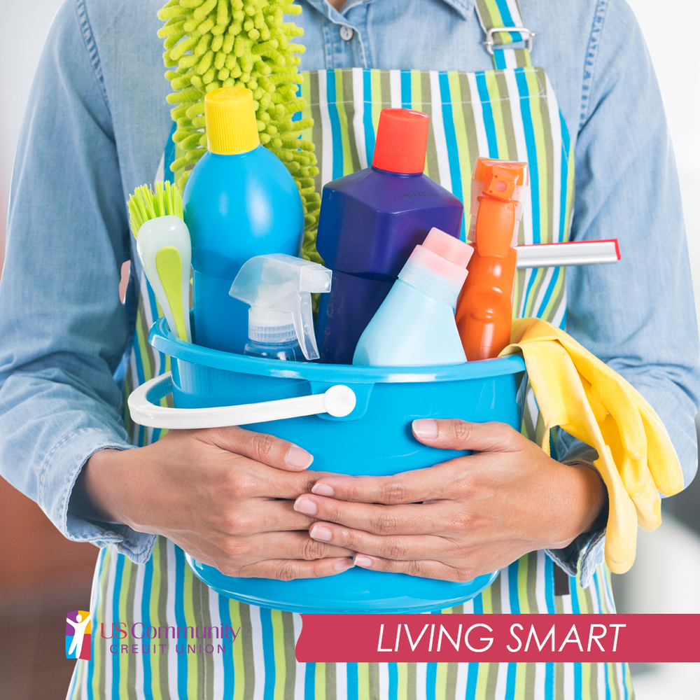 A man in an apron holding multiple cleaning bottles and brushes