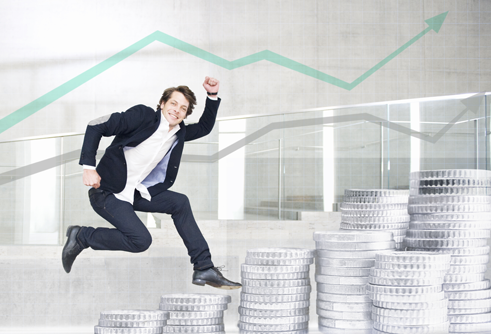 man jumping over giant coins