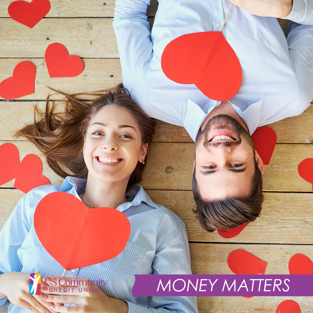 A young couple holding paper hearts