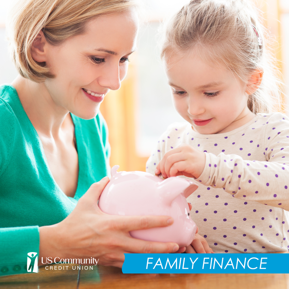 A mom holding a piggy bank while her young daughter puts coins into it