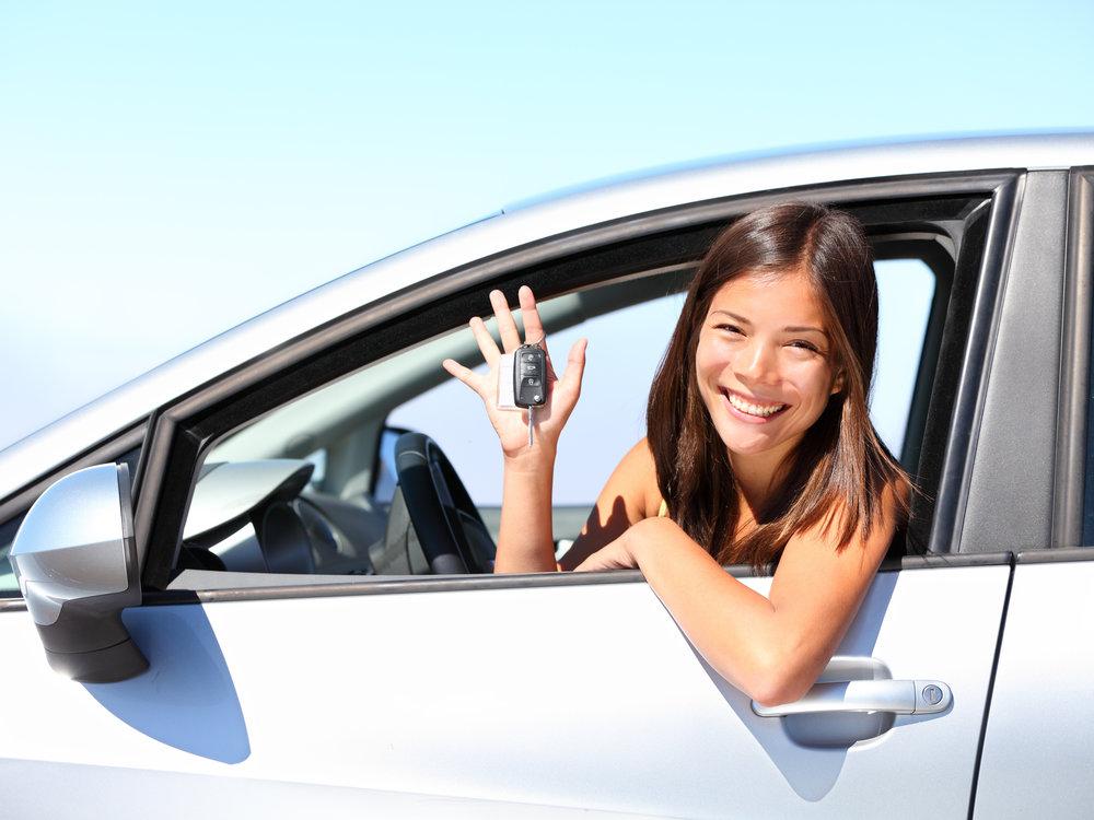 Girl sitting in new car holding keys