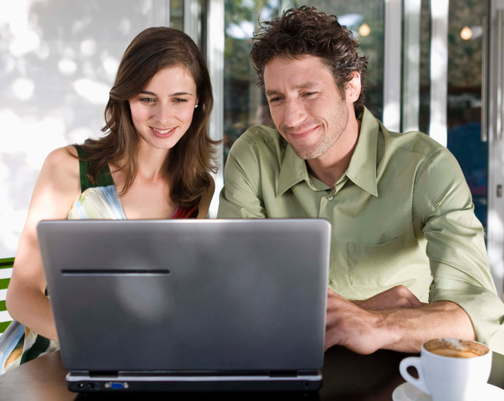 Happy man and woman looking at their laptop, paying bills online.