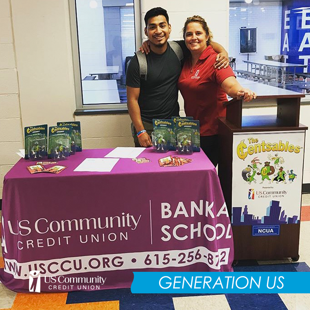 Two people standing behind a credit union table in a school.