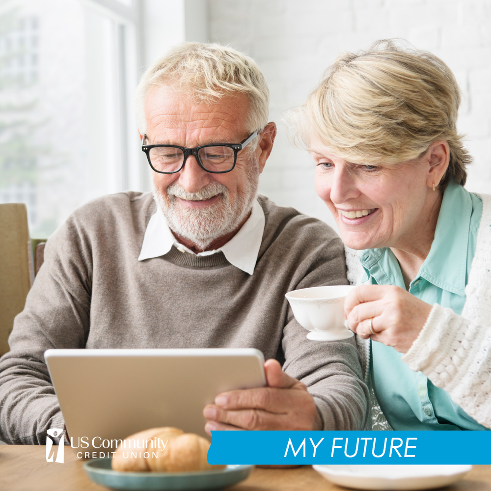 Two older people smiling looking at an iPad while the woman holds a tea cup.