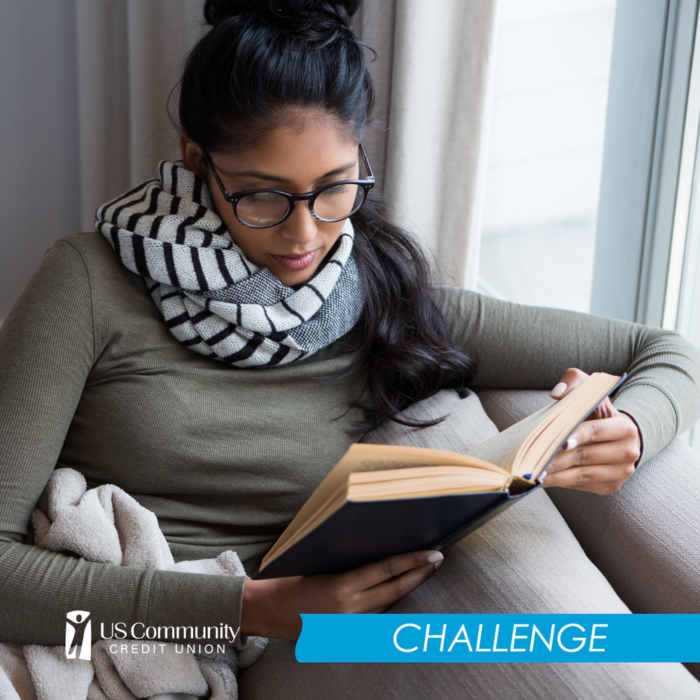 Woman sitting on the couch reading a book.