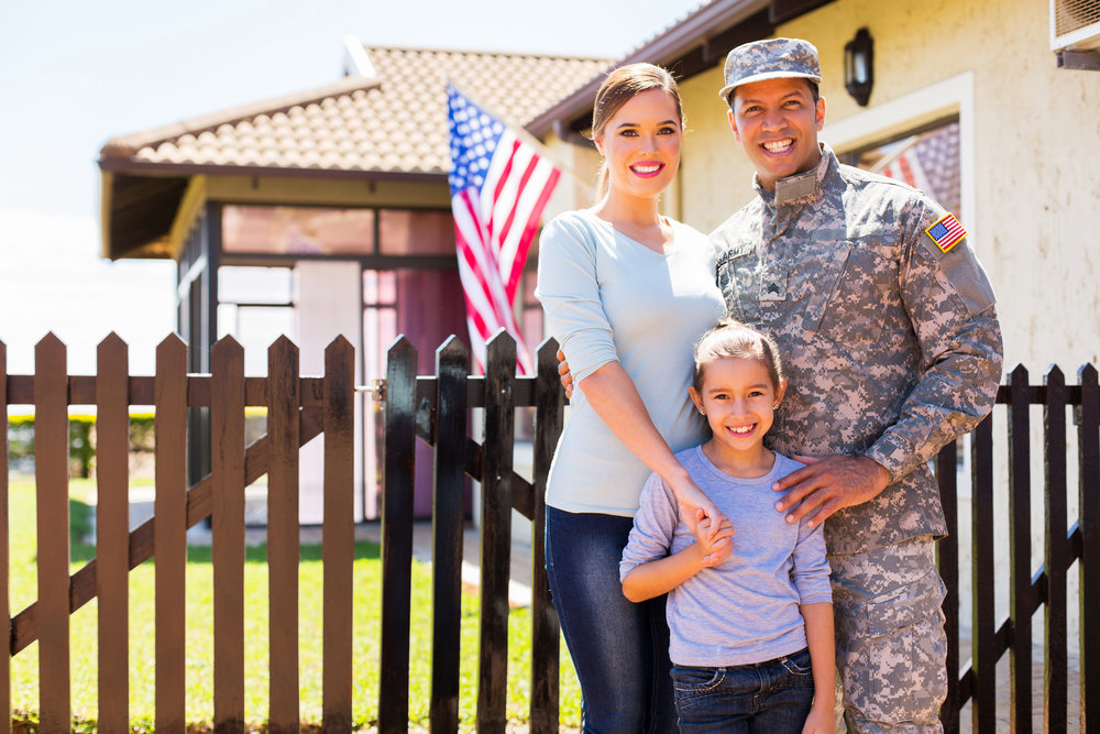 A soldier standing with his family in front of a house