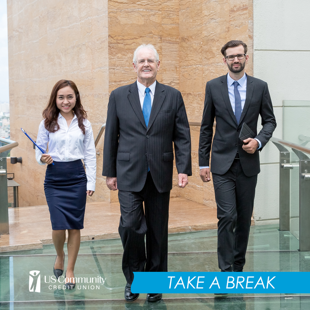 Three people in business clothes walking forward.