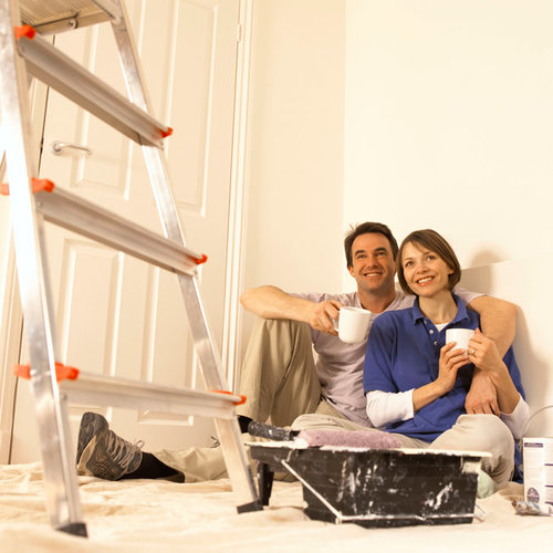 A happy couple, sitting behind a step ladder and house paint supplies, admiring their work.