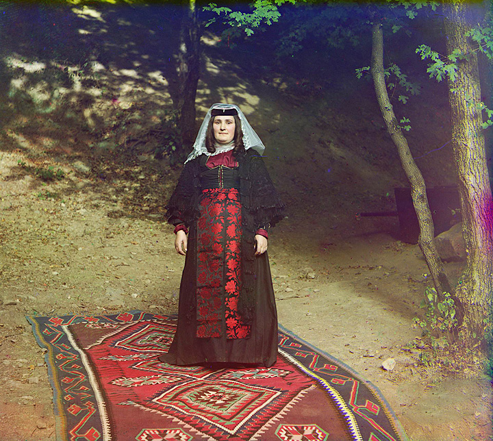 Georgian woman standing on a carpet, outside, near a tree. 1905-1915.