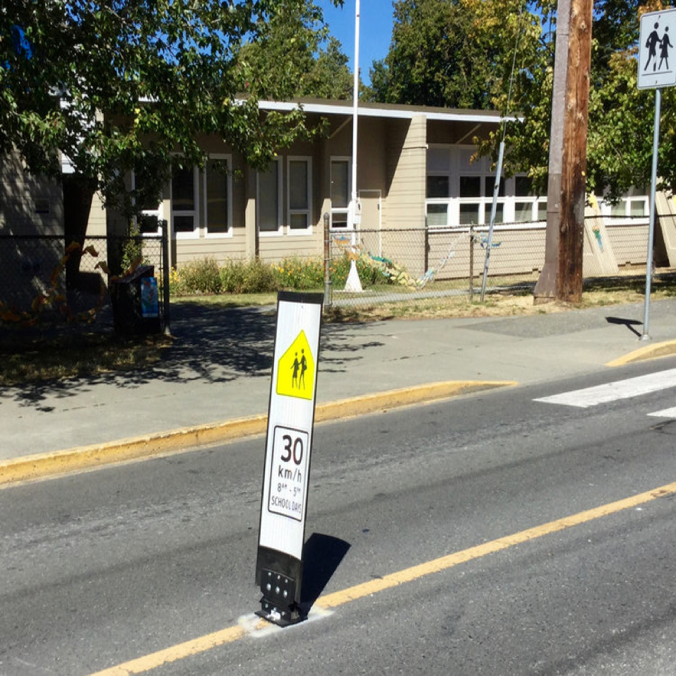 New signage and centre-line barriers on Oswego Street help to slow traffic and draw attention to speed limits in the area of the school.   Photo by Robert Hawkes