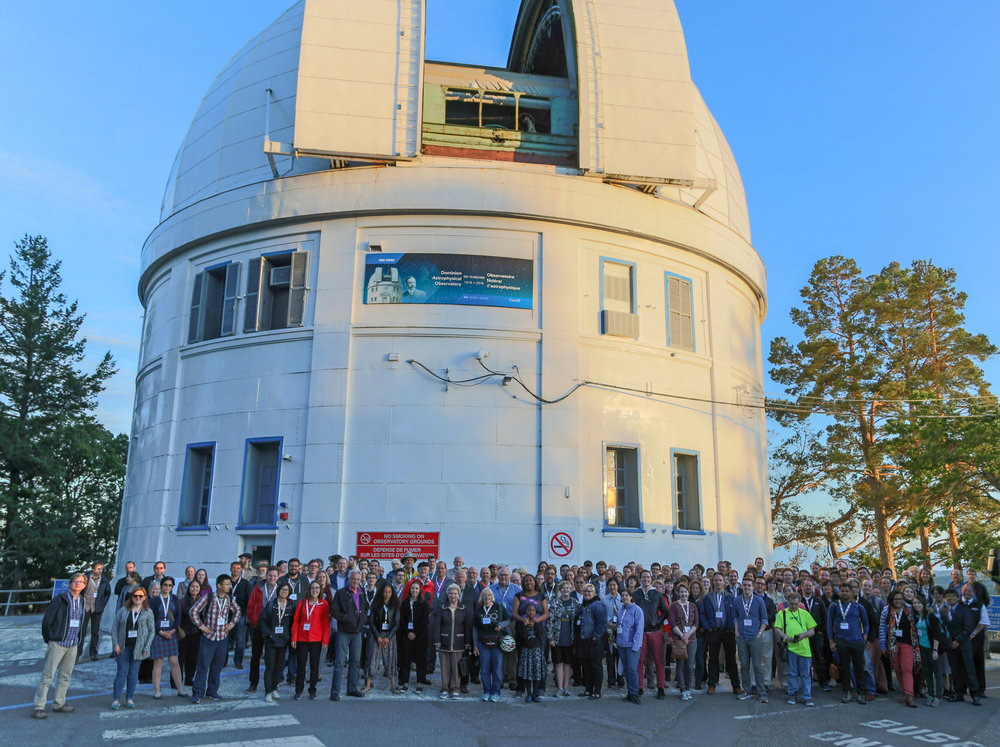 Canadian astronomers met in late May to celebrate the anniversary of first light at the Plaskett Telescope. Here they are pictured just outside the building that houses the telescope. Photo is by Victoria photographer Joe Carr.