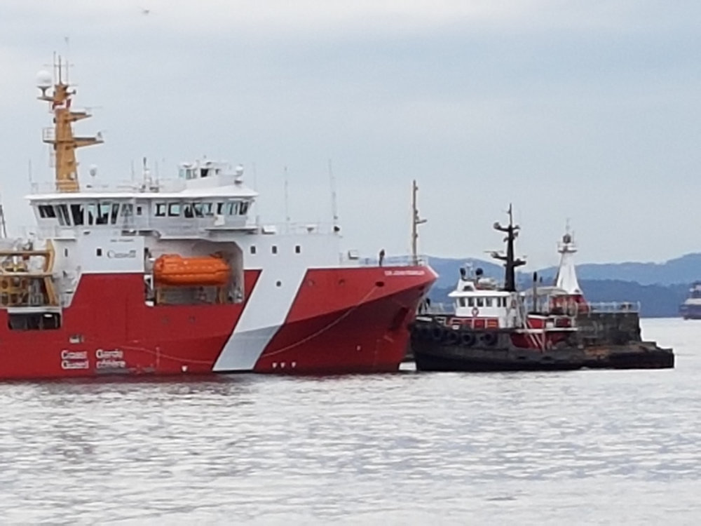 Tug boats assist new Coast Guard ship that struck the Breakwater on its very first test voyage on March 22.  Photos by Don Allan