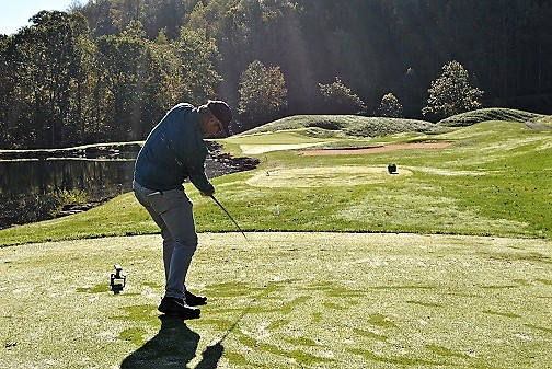 Mike hits his tee shot on the fourth hole.