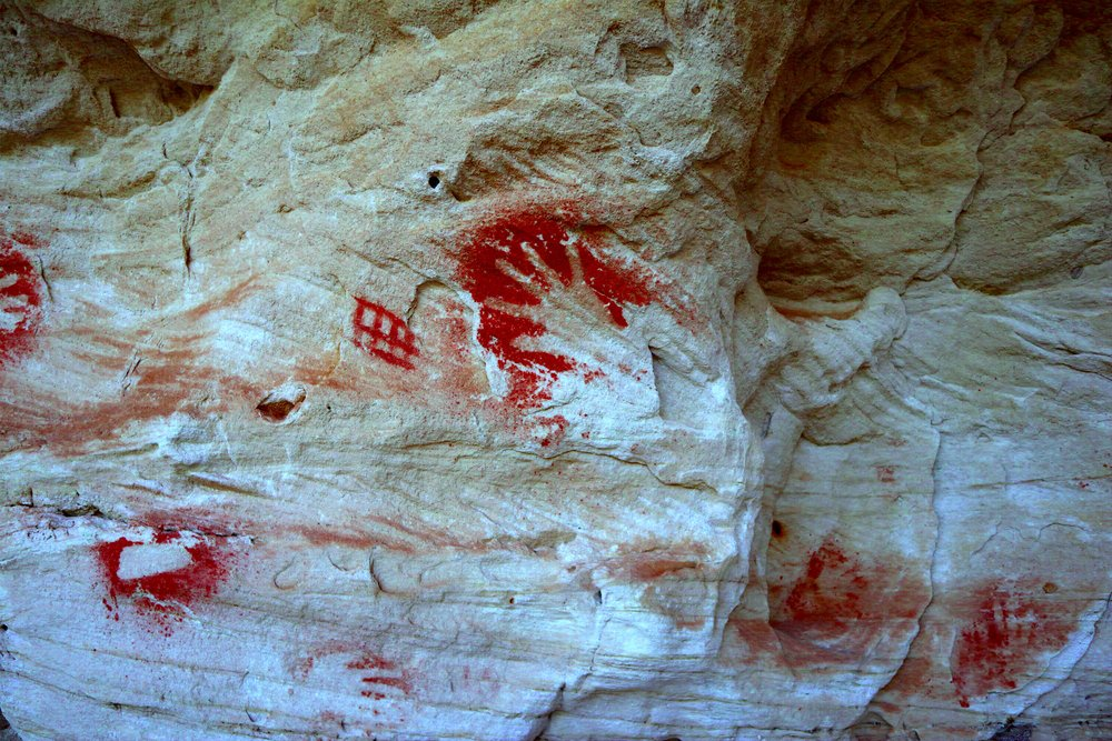 Ruined Castle Creek rock art site 1 showing yellow ochre boomerang stencil with superimposed hand stencils in red ochre. (NPAQ Library)