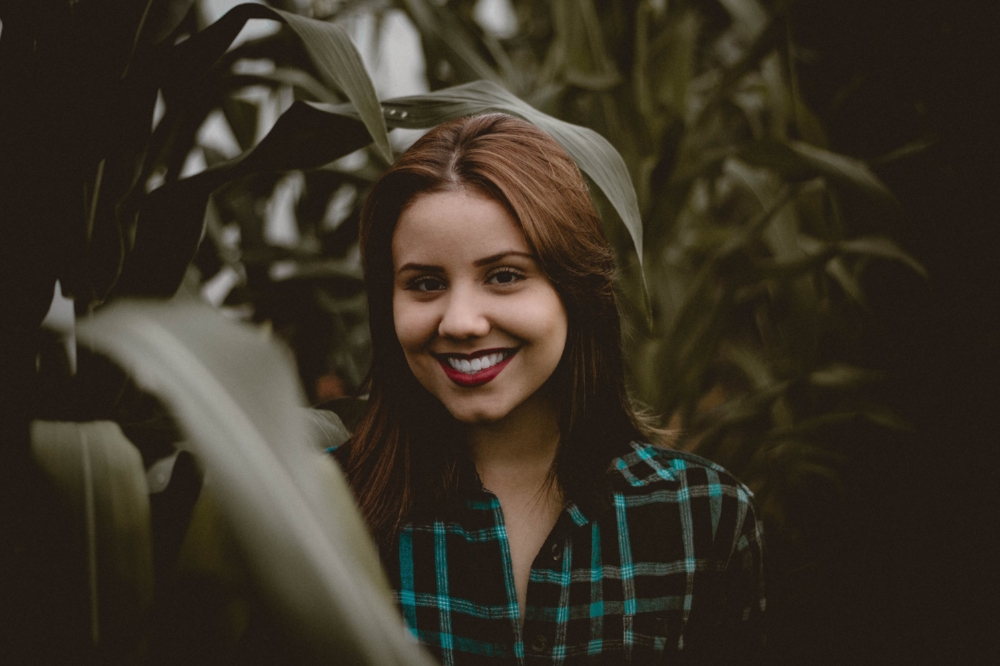 Trauma-counselling-for-Complex-Trauma-and-PTSD-in-Melbourne-with-Melburne Psychotherapist-Amanda-Robins-Young-girl-in-plaid-shirt-surrounded-by-foliage-smiling happily.